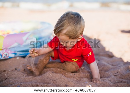 little boy play with sand on summer beach, looking down