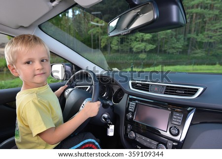 Little boy play with steering wheel in  car