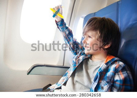 Little boy play with toy plane in the commercial jet airplane flying on vacation - stock photo