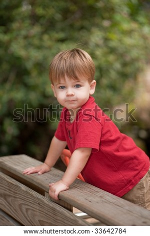little boy playing at a playground - stock photo