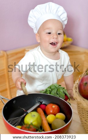little boy playing cooking with fresh fruit and vegetables