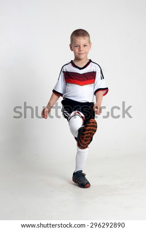 little boy playing football.Isolated studio portrait - stock photo