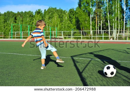little boy playing football on football pitch