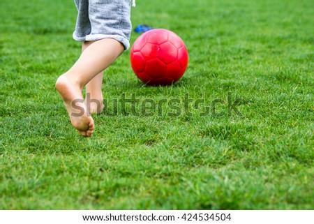 Little boy playing football on green grass - stock photo