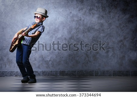 Little boy playing guitar on a grey wall background - stock photo