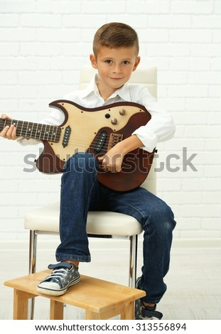 Little boy playing guitar on light background - stock photo