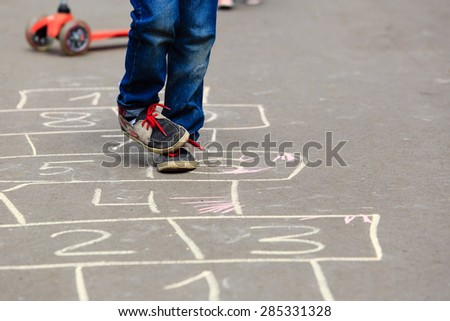 little boy playing hopscotch on playground outdoors - stock photo