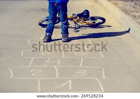 little boy playing hopscotch with bike outside - stock photo