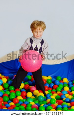 little boy playing in playground colorful ball pool - stock photo