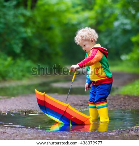 Little boy playing in rainy summer park. Child with rainbow umbrella, waterproof coat and boots jumping in puddle and mud in the rain. Kid walking in autumn shower. Outdoor fun by any weather