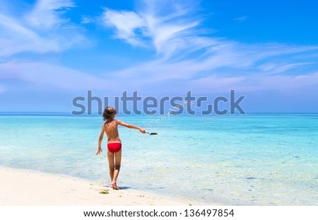Little boy playing in sand on a beautiful tropical beach