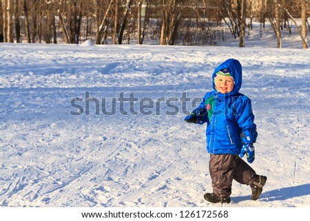 Little boy playing in snow winter - stock photo