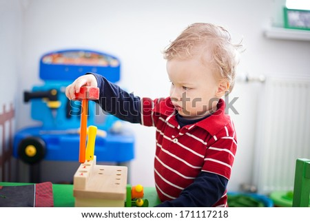 Little boy playing in the kindergarten - stock photo