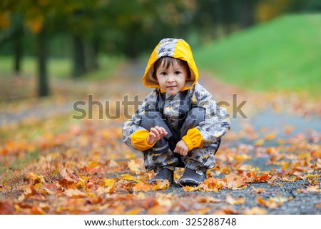 Little boy, playing in the rain in autumn park, leaves around him - stock photo