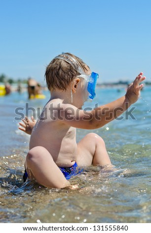 Little boy playing in the sea sitting in shallow water wearing goggles splashing around in excitement - stock photo