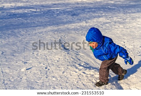 little boy playing in winter snow - stock photo