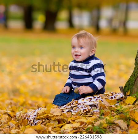 Little boy playing in yellow foliage. Autumn in the city park