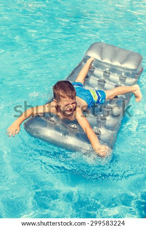Little boy playing on air mattress in water - stock photo