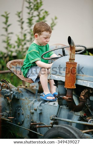 Little boy playing on an old abandoned tractor