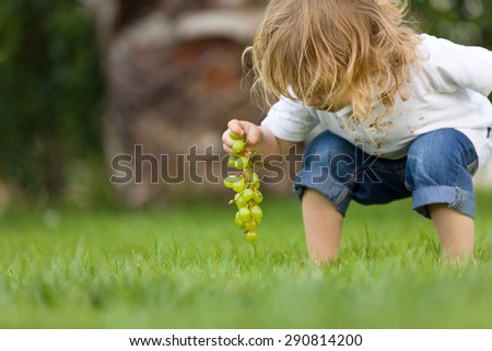 Little boy playing on grass. - stock photo