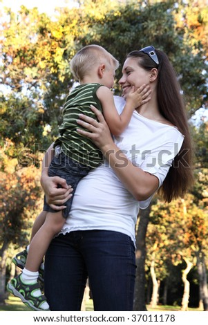 Little boy playing on mother's arms at park