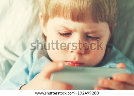Little Boy Playing on Smartphone, Sitting in Room, toned image - stock photo