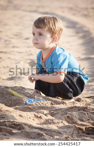 Little boy playing on the beach in sand with bucket and spade