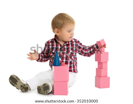 Little boy playing on the floor , he builds the cubes of the pink pyramid. Montessori kindergarten - Isolated on white background - stock photo