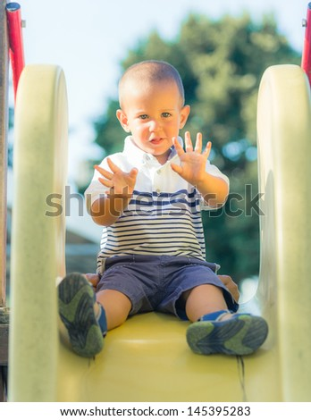 Little Boy Playing on the Slide at Park