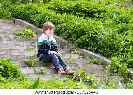 Little boy playing on the stairs on a garden - stock photo