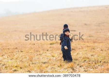 Little boy playing outdoor in spring landscape. Happy caucasian child - stock photo