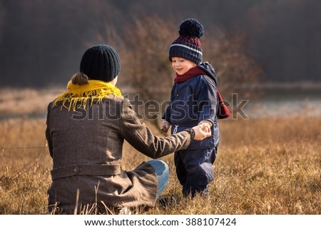 Little boy playing outdoor in spring landscape. Happy caucasian child playing with his mother - stock photo