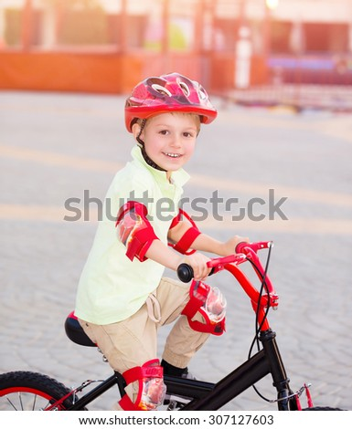 Little boy playing outdoors, cute cheerful child having fun in summer camp, riding on red stylish bicycle, enjoying carefree summer holidays
