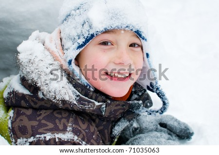little boy playing outdoors in the snow - stock photo