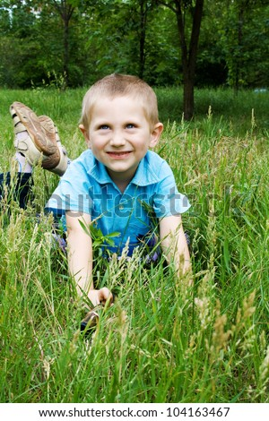 Little boy playing outdoors, lying on green grass