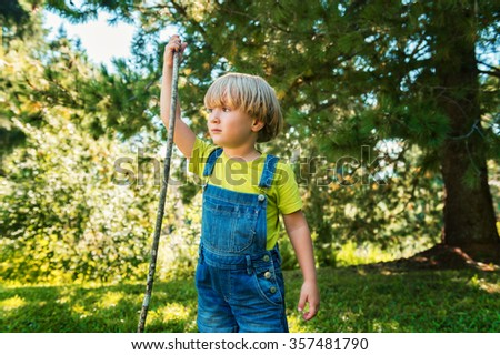 Little boy playing outdoors on a nice sunny summer day wearing denim overalls