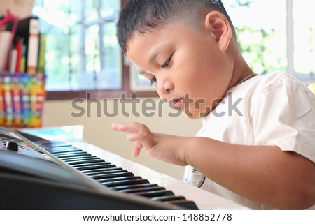 Little Boy playing piano fun - stock photo