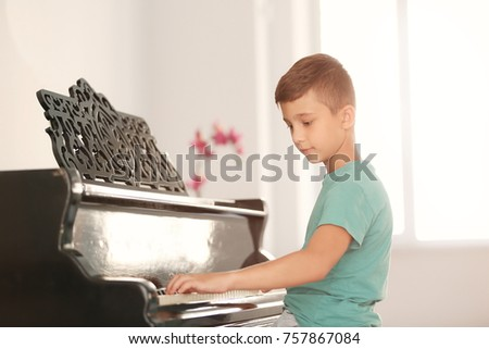 Little boy playing piano indoors