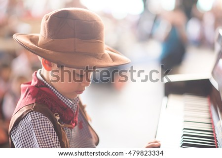 Little boy playing piano outdoor performance