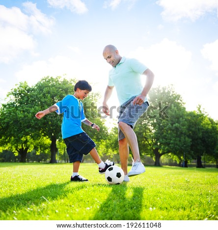Little boy playing soccer with his father. - stock photo