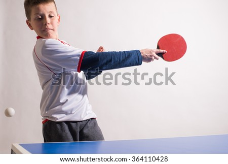 little boy playing table tennis - stock photo
