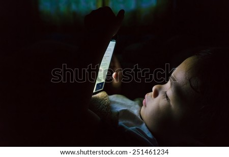 Little boy playing tablet on night. Light coming from the tablet. - stock photo