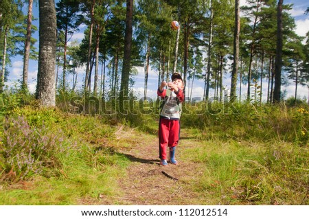 Little boy playing with a ball in the forest