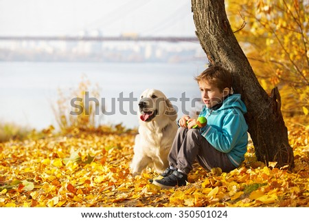 Little boy playing with a golden retriever in autumn park - stock photo