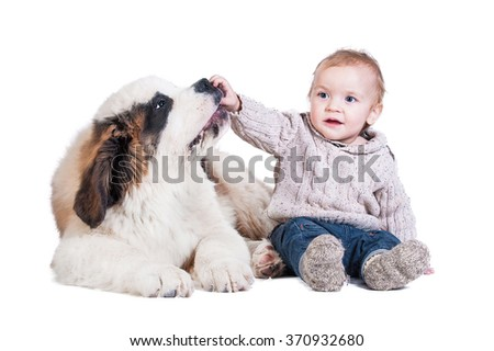 Little boy playing with a saint bernard puppy