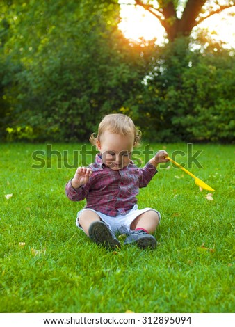 Little boy playing with a spatula sitting on the grass.