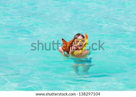 Little boy playing with a star fish on a tropical beach - stock photo