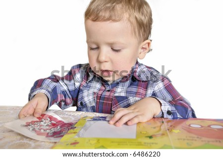 little boy playing with book isolated on a white background