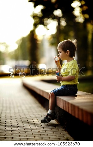 little boy playing with bubbles - stock photo