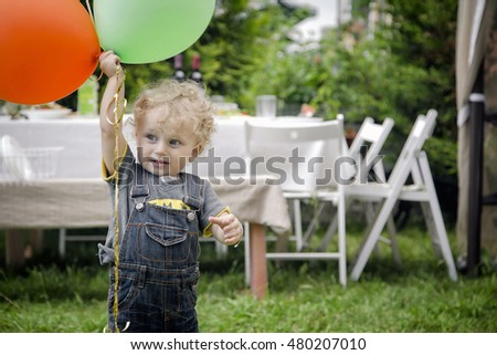 Little boy playing with colorful balloons
